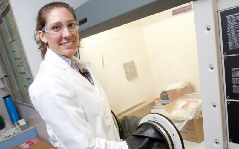 Ale Hakala smiling at the camera wearing safety goggles and a lab coat while using an anaerobic chamber in a lab