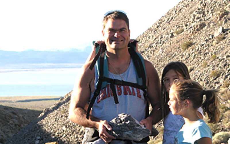 Denis Balcer hiking with his two young daughters and examining rocks
