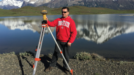 Julio carrying out field work in an OSU sweater in front of a mountain lake