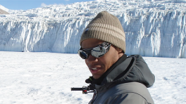 Derrick Lampkin doing field work in front of a glacial background