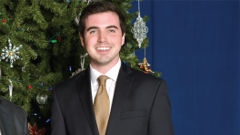 Sean O'Brien smiles in a suit in front of a Christmas tree