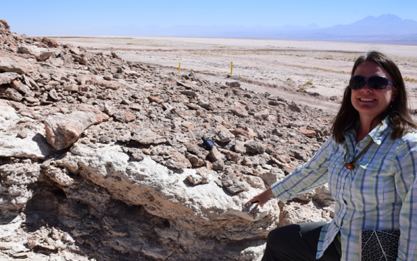 LeeAnn Munk smiles at the camera wearing sunglasses and field attire while pointing to a rock. She is in the field--Salar de Atacama collecting carbonate samples.