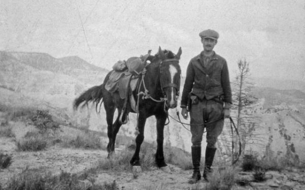 black and white photo of edmund spieker doing field work while leading a horse