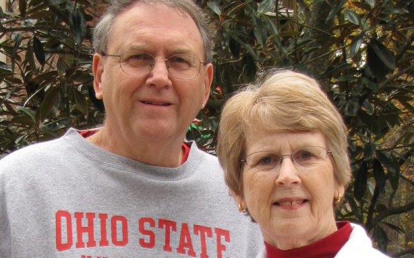 Mike and Cindy Morgan smiling at the camera. Mike is wearing an OSU sweatshirt and Cindy is wearing a Wittenburg sweatshirt.