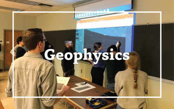 "Photo of students in class interpreting seismic data on a projection. Overlain text that reads, ""Geophysics"""