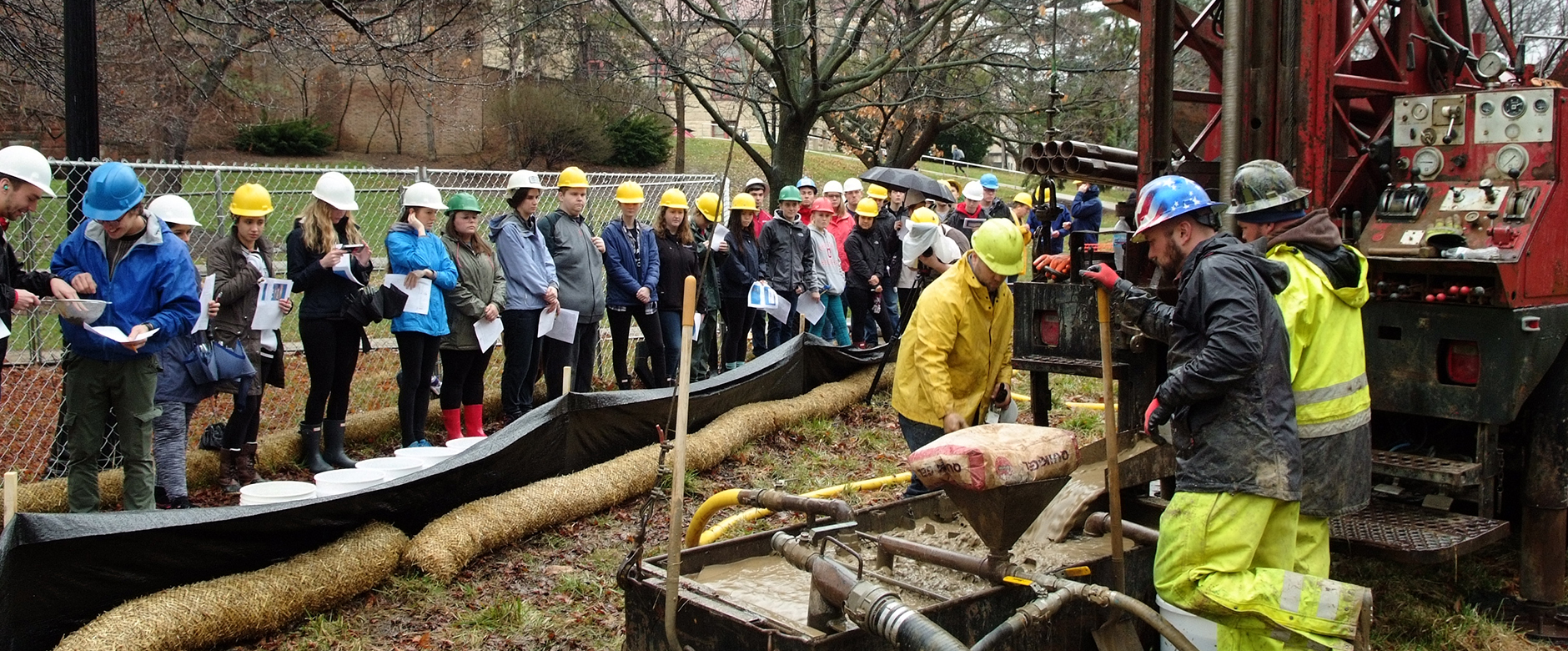 Photo of SES students and Professor Audrey Sawyer looking at borehole cuttings